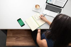 Person Taking Note in Notebook next to Macbook and Phone