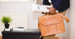 Man holding Leather Bag and Newspaper