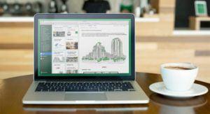 Foto de um computador em cima de uma mesa redonda ao lado de uma xícara de café
