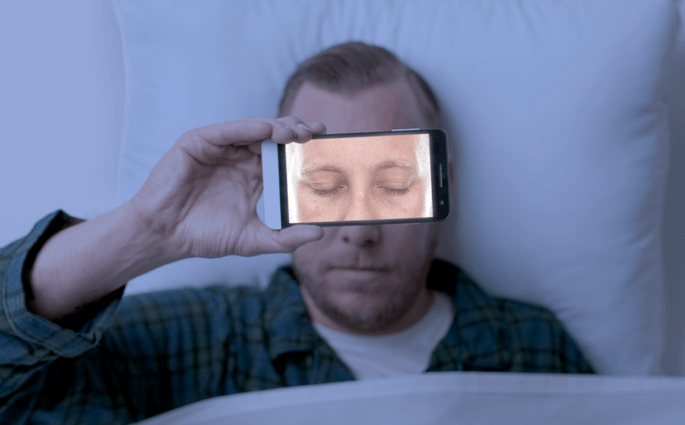 Man with a smartphone over his face