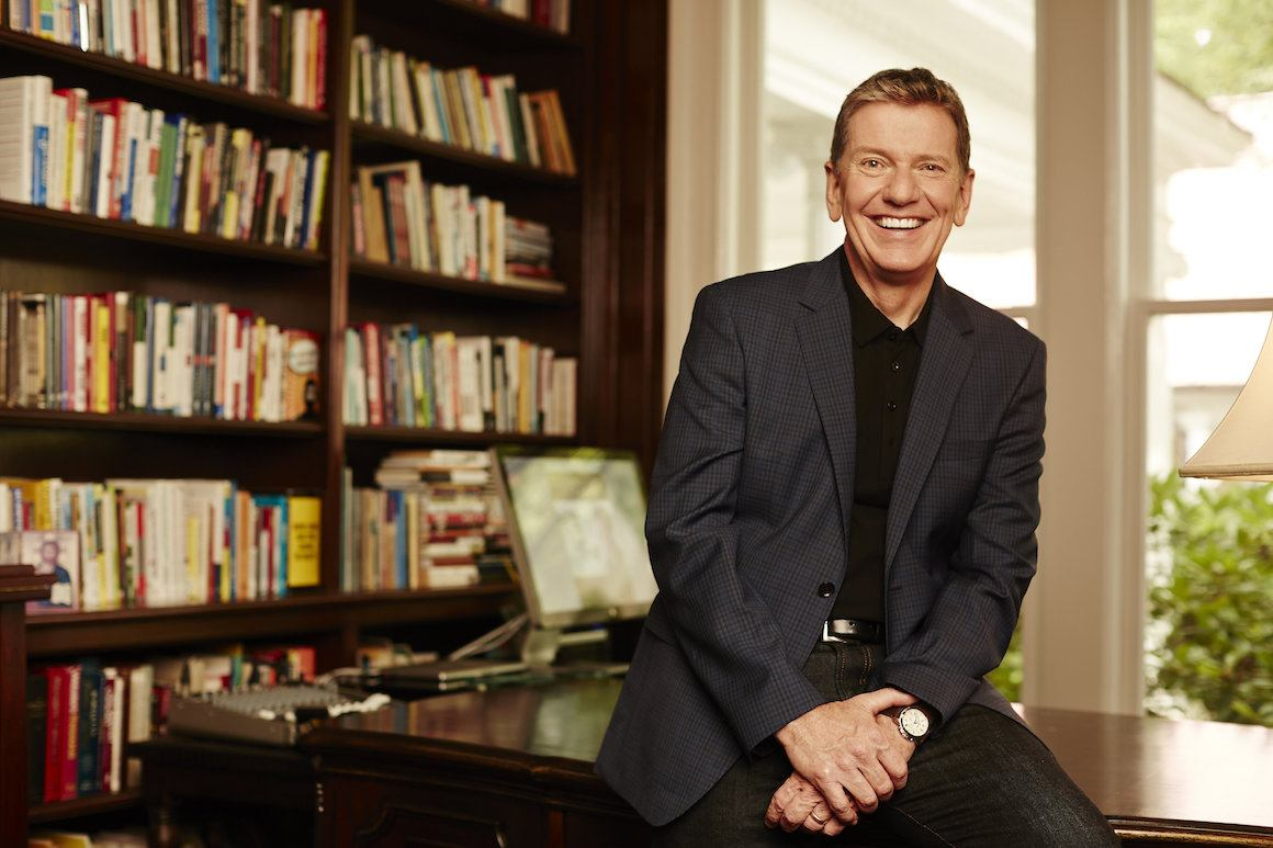 Michael Hyatt Sitting on a Desk in Front of Bookcase