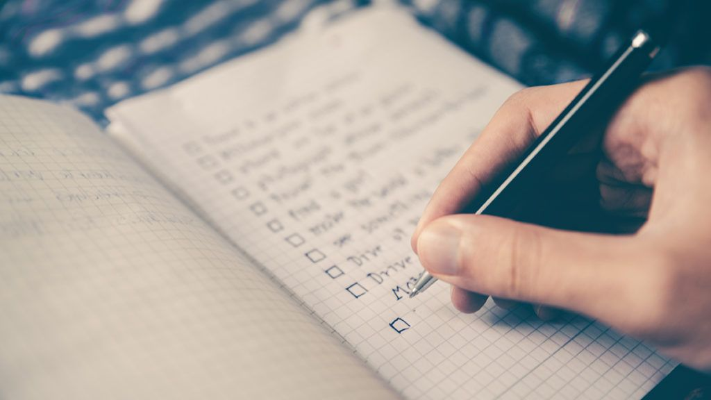 Person Writing a Checklist in a Notebook