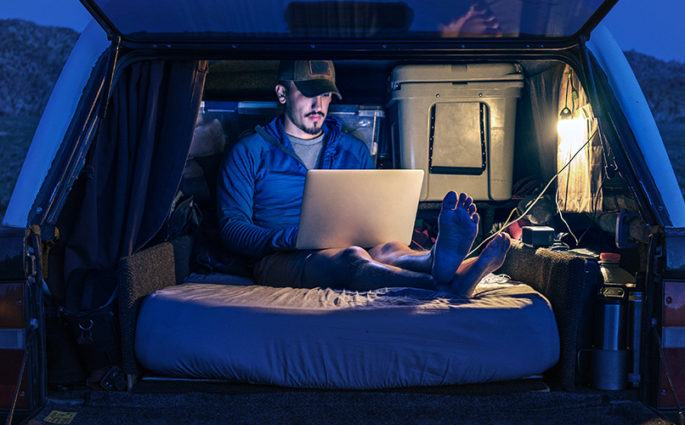 Guy sitting on a mattress in the back of his car working on a laptop