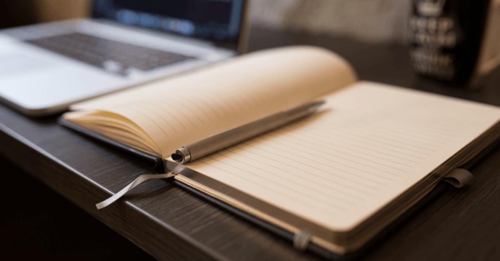 Empty Open Notebook with Pen next to Macbook