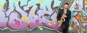 Jazz saxophonist Mike Casey playing while standing in front of a wall of graffiti.