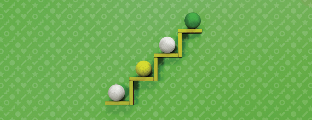 Four wooden balls on a rising platform, set against a patterned background.