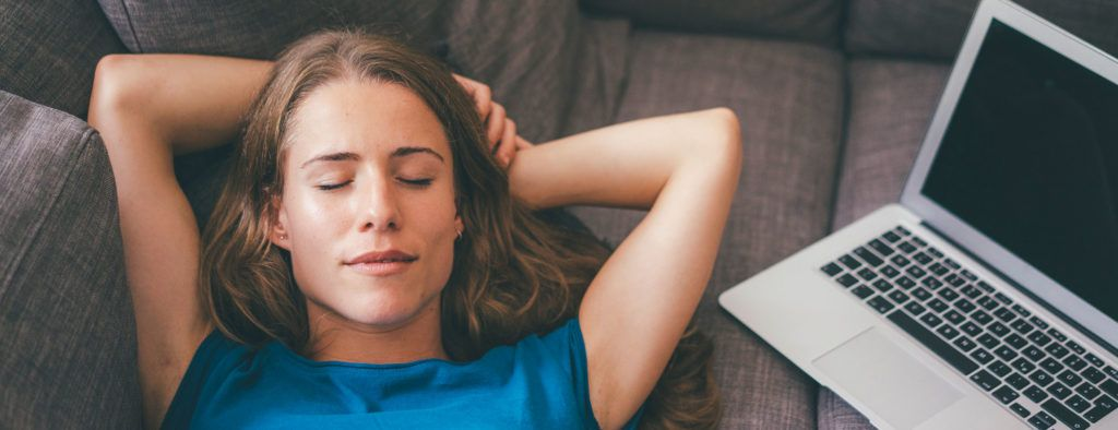 Image of a woman in a blue shirt sleeping on a sofa with a laptop beside her.